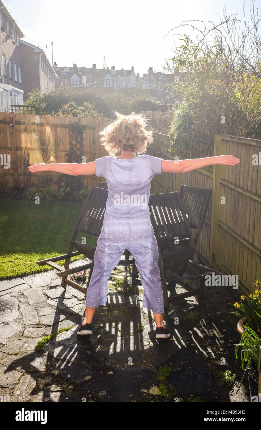 Mature middle age Wiman doing health and fitness star jumps exercises in back garden at home in early morning sunlight - Stock Image