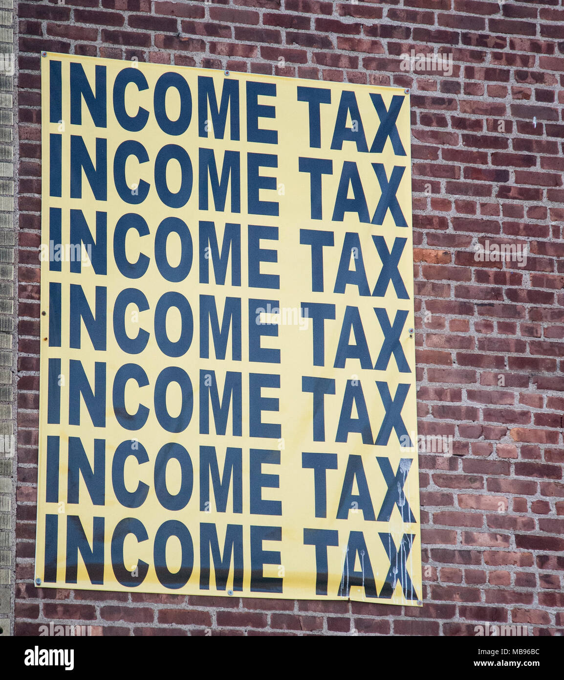 Income tax sign on the side of a building in Paterson, NJ - Stock Image