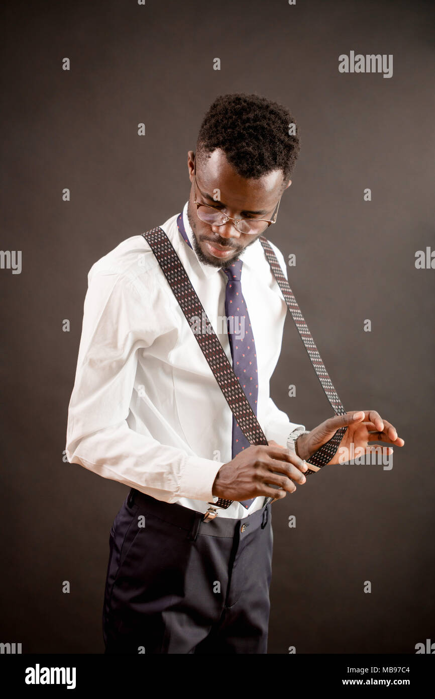 portrait of African male looking at his new trousers with suspenders - Stock Image