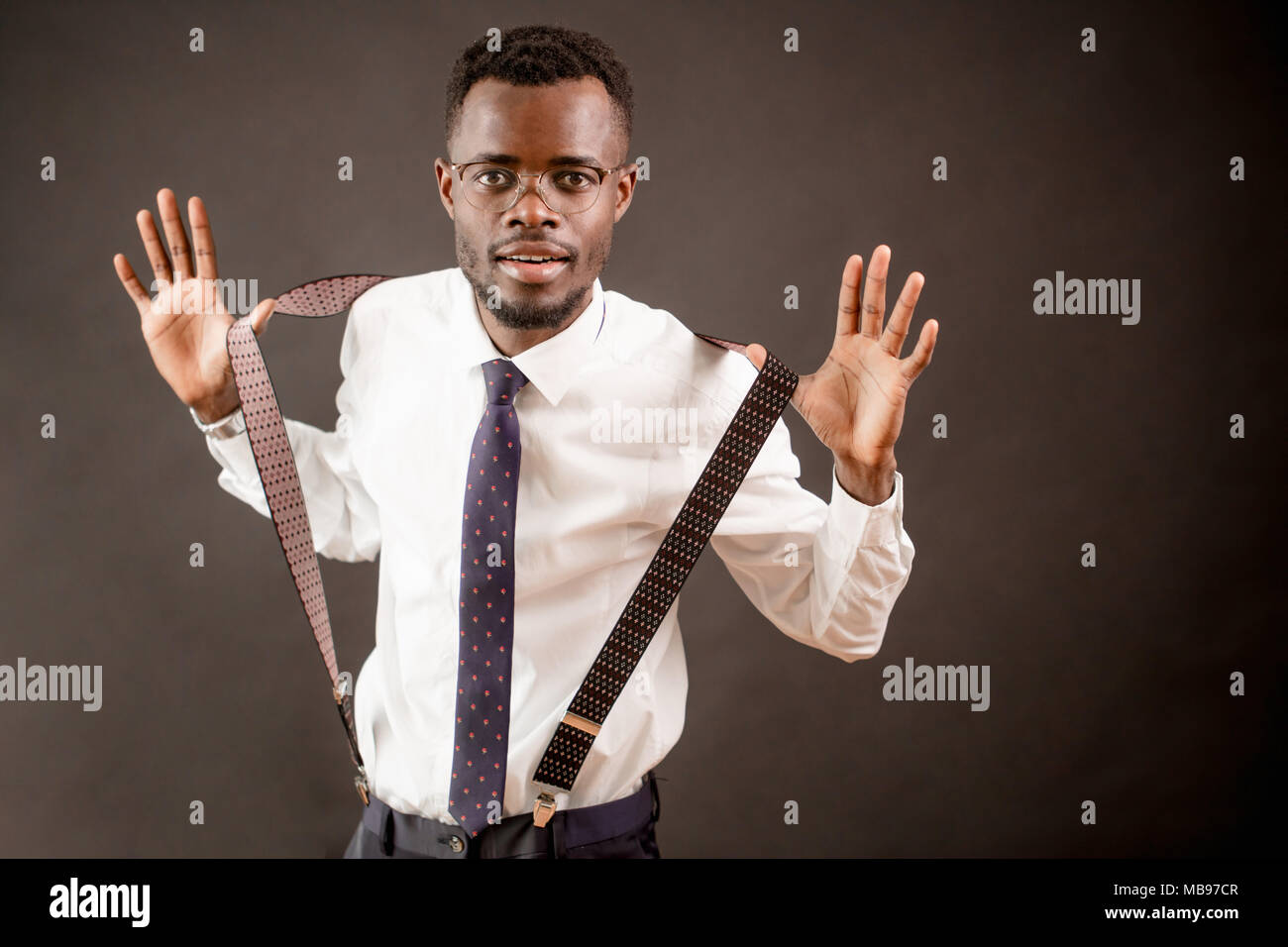 close up shot of African teacher in glasses pulling his suspenders - Stock Image