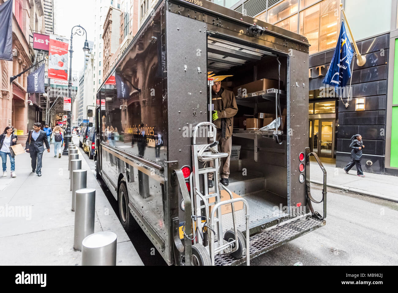 New York City, USA - October 30, 2017: UPS, United Parcel Service, man unloading packages delivery at Broadway St by Wall Street in NYC Manhattan lowe - Stock Image