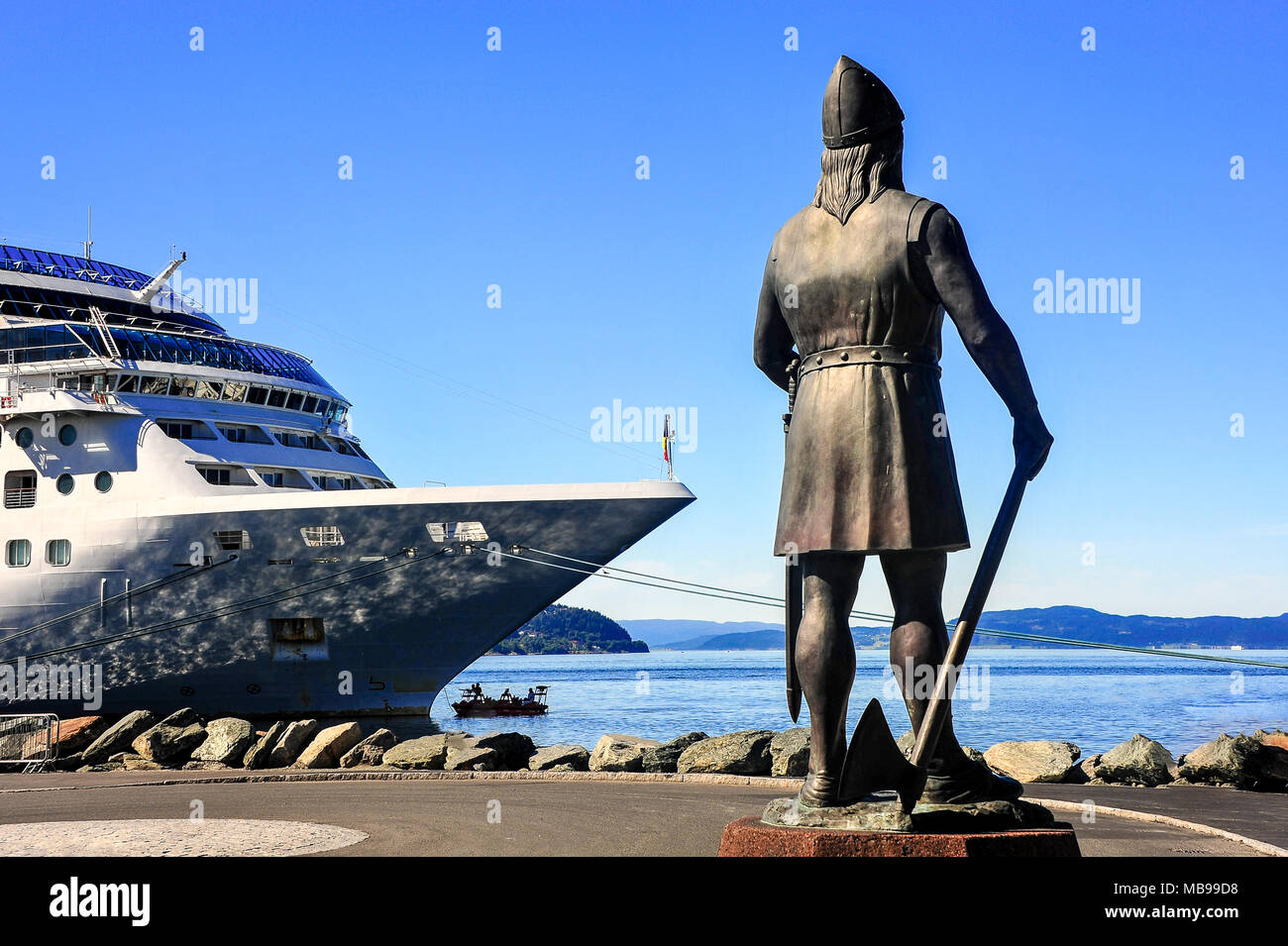 Leiv Erikson statue looks seaward silhouetted against blue sky background. Bronze figure with sword and axe, standing by bow of large cruise liner - Stock Image