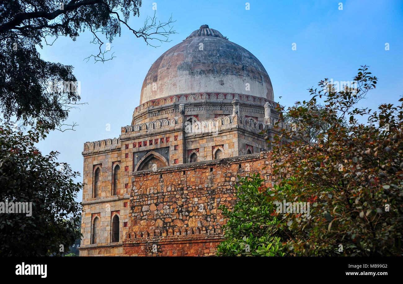 View to Bara Gumbad (big dome) mosque in the Lodi Gardens, New Delhi, India. Colourful square building with hemispherical dome against blue sky - Stock Image