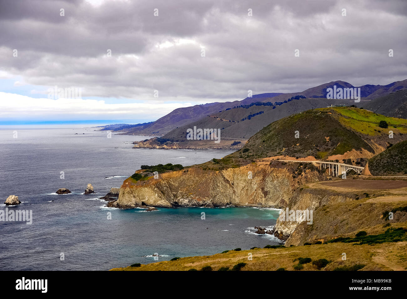 Aerial view of Bixby Creek Bridge, Cabrillo Highway 1, California, USA. Coastal landscape, Pacific ocean, rolling green hills and grey cloud skies - Stock Image