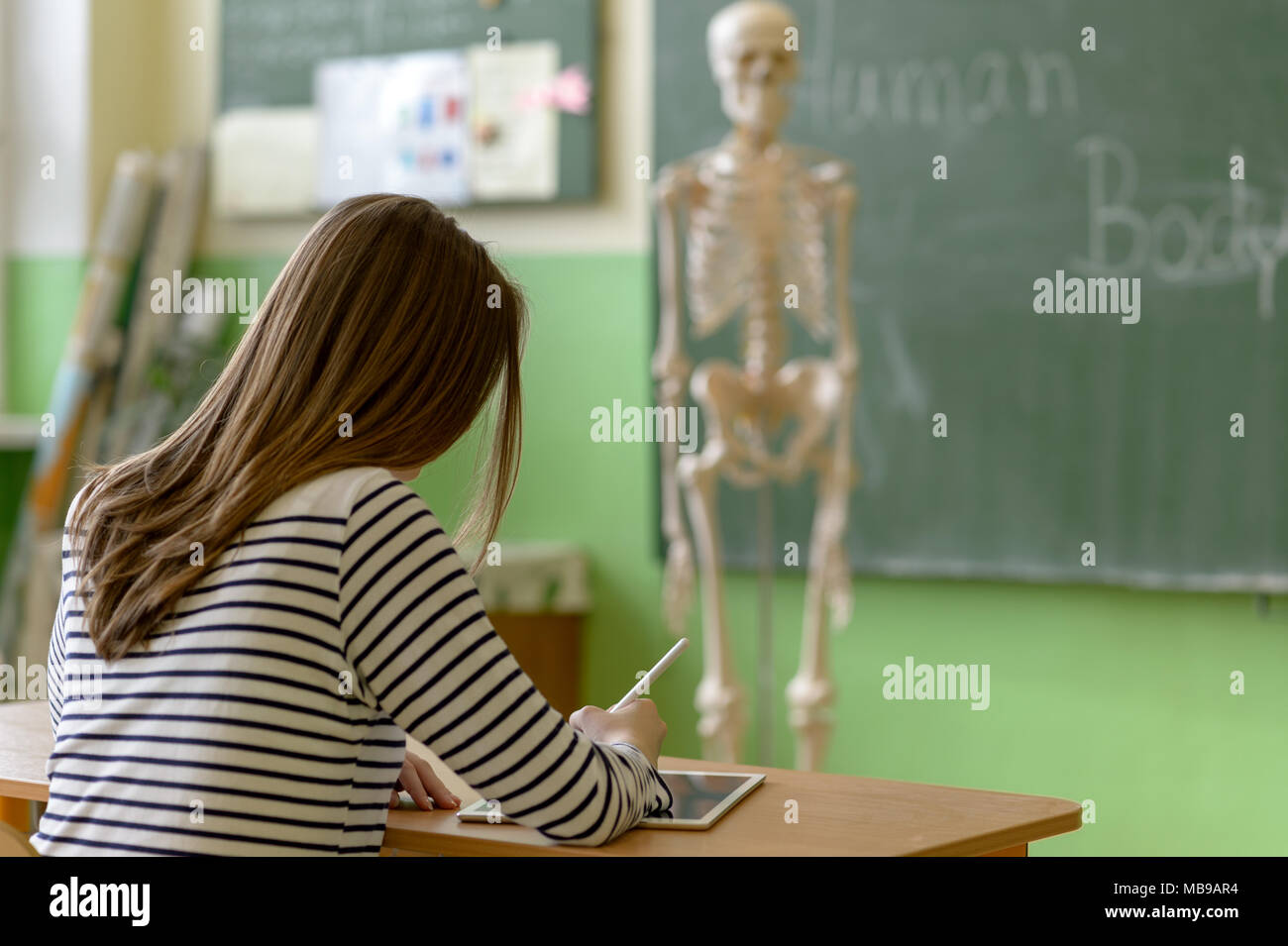 Female student writing notes using digital tablet in biology class. Generation Z Education concept. - Stock Image