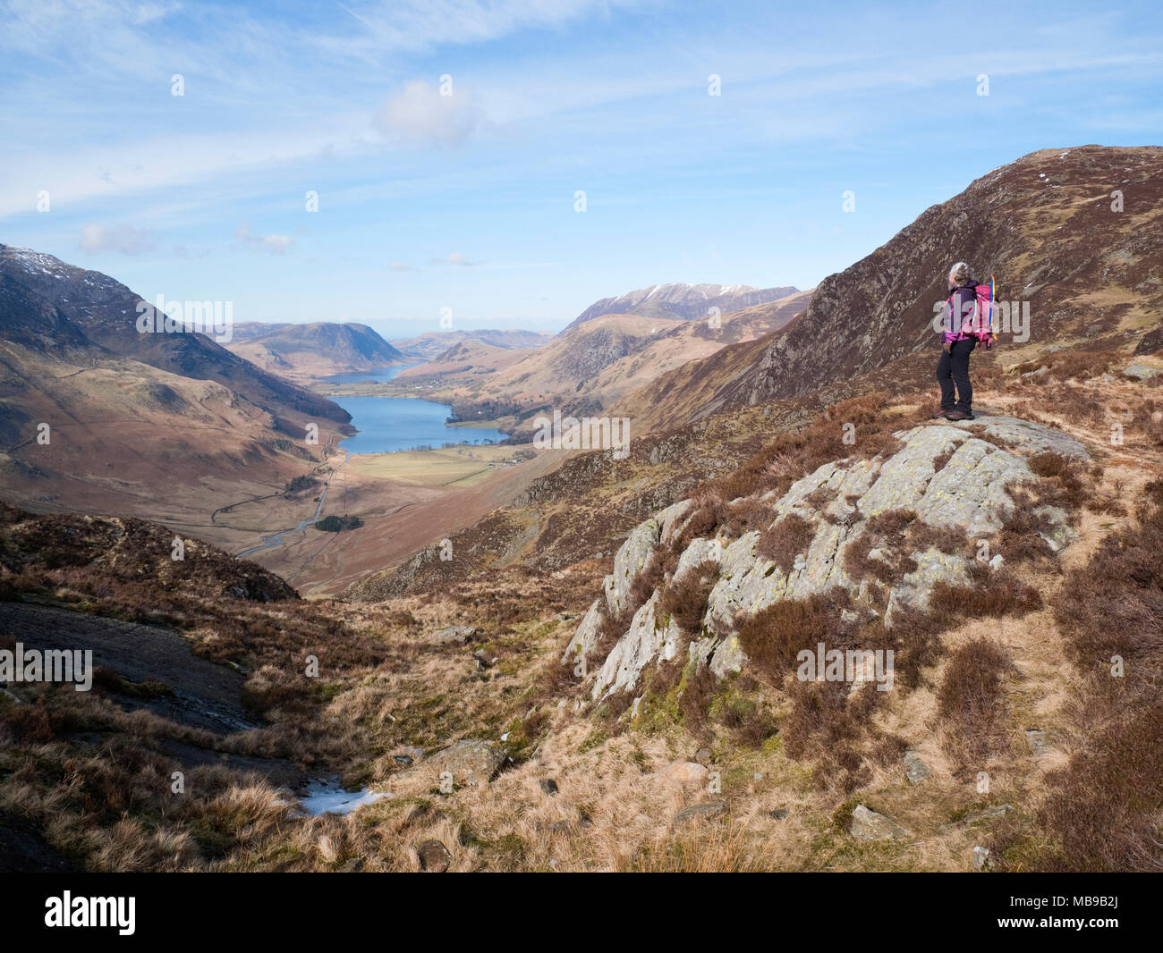 Female hiker admires view from Little Round How, Fleetwith Pike along Warnscale Bottom to Buttermere, with Mellbreak rising over Crummock Water beyond Stock Photo
