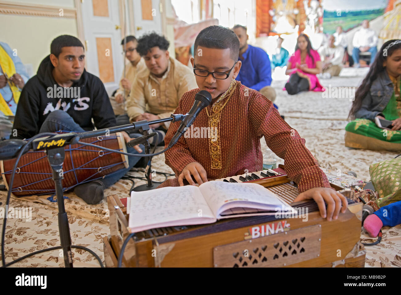 A teenage Hindu boy sings and plays the piano at morning services at at the Tulsi Mandir temple in South Richmond Hill, Queens, New York. - Stock Image