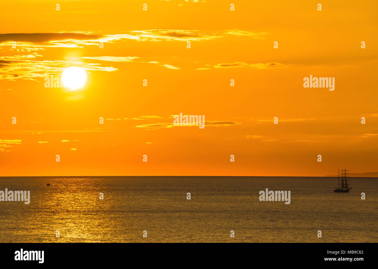 Beautiful sunset above the sea and small boat - Stock Image