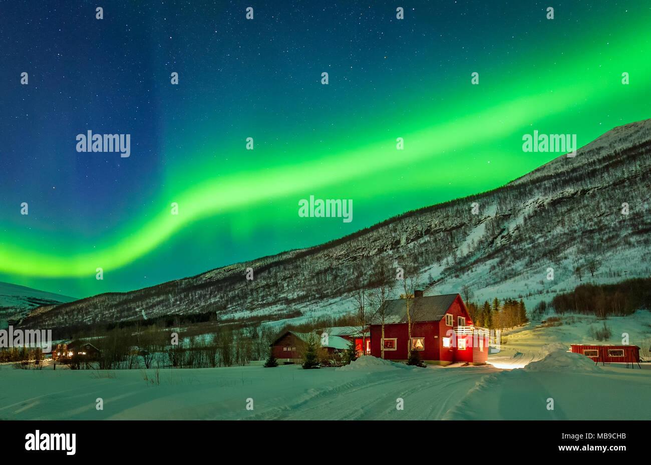 Aurora Borealis over mountain and rural house in distant Northern Norway. Green light of aurora lay over mountains. - Stock Image