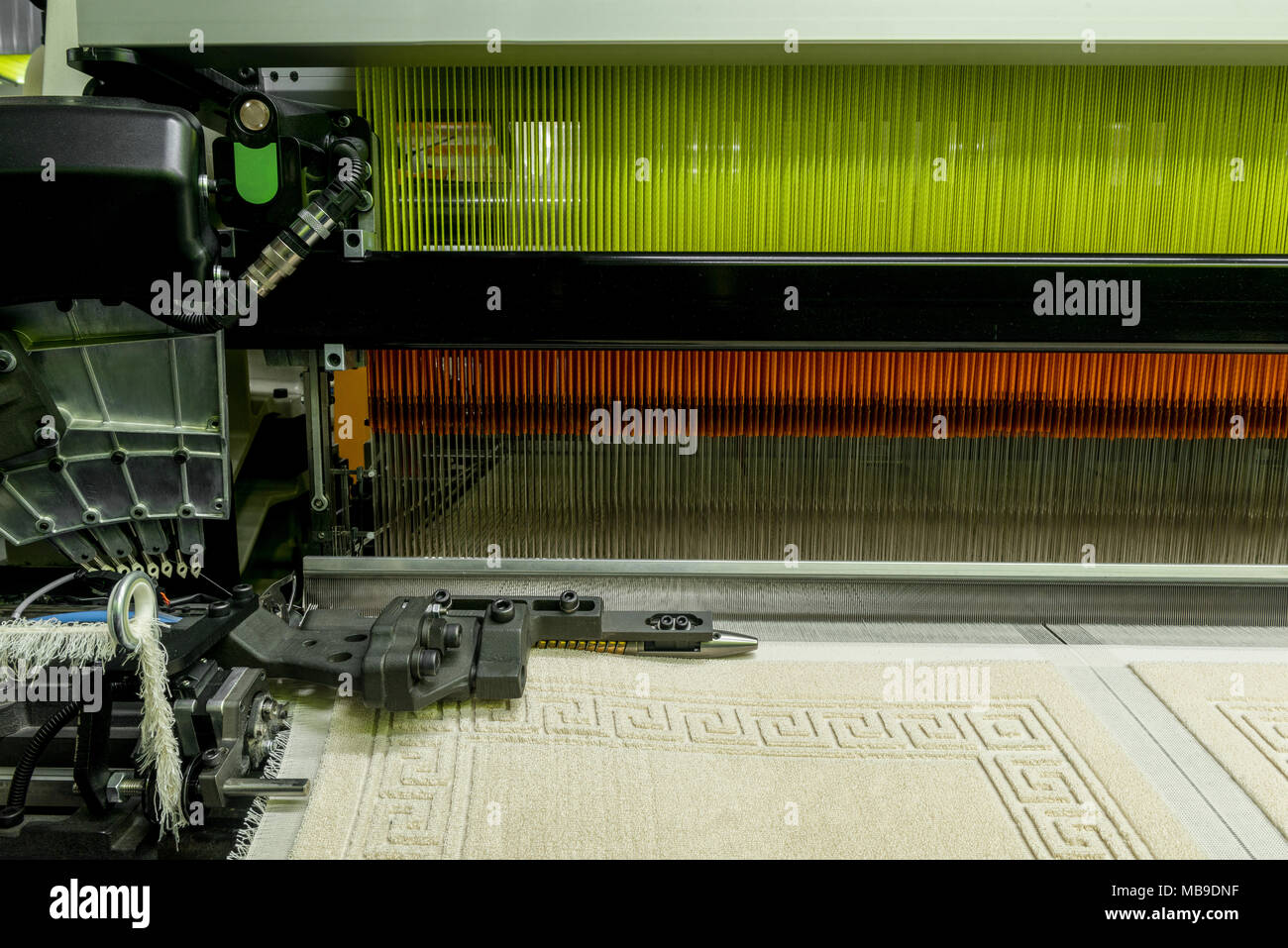 weaving loom at a textile factory, closeup. industrial fabric production line - Stock Image
