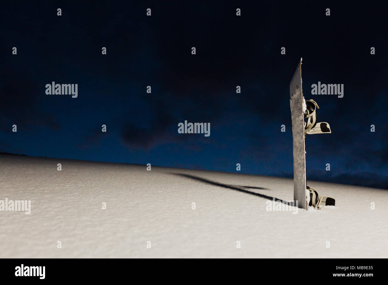 Powder texture and snowboard at sunset - Stock Image