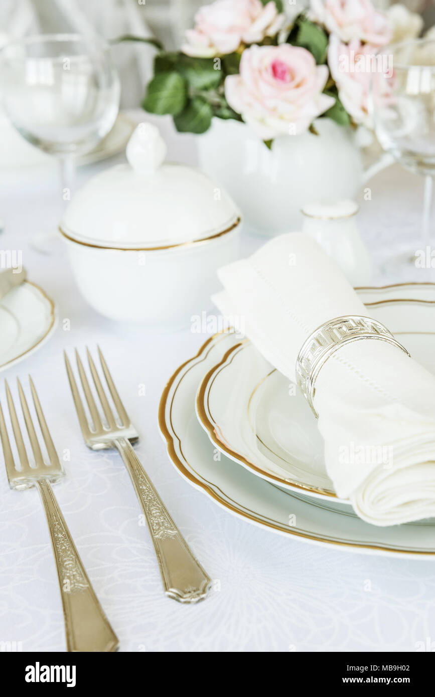 Beautifully decorated table with white plates, glasses, cutlery and flowers on luxurious tablecloths - Stock Image