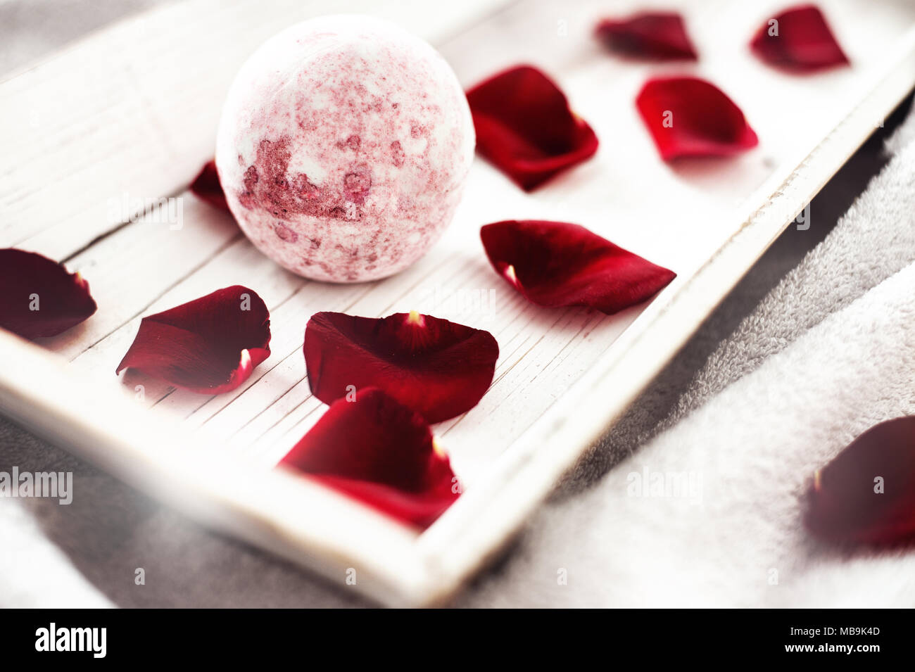 Bomb salt bath decorated with dried roses on a white background - Stock Image