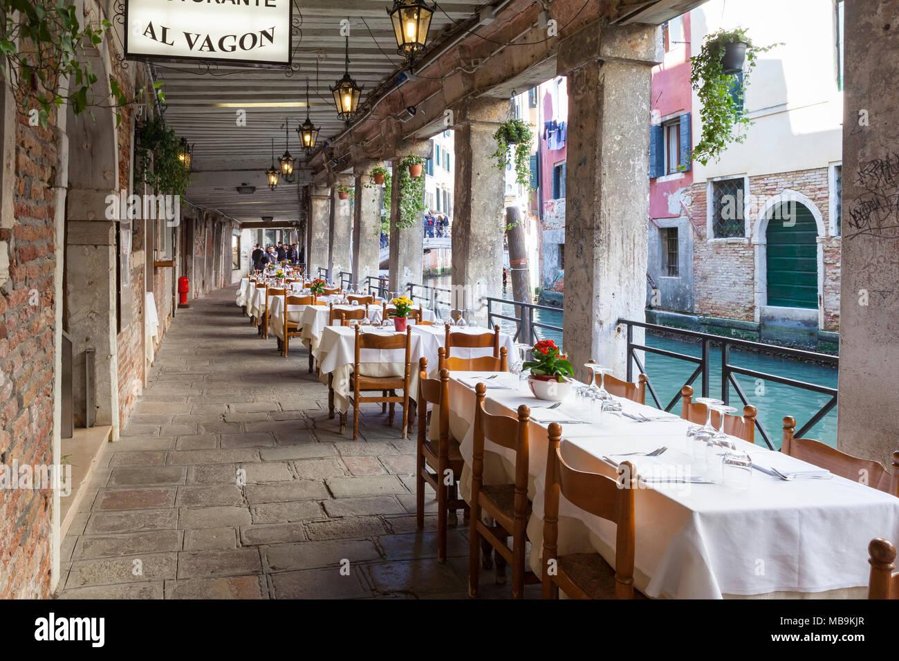 Tables under  sotoportego Magazen (undercover walkway) at Ristorante Al Vagon, Cannaregio, Venice, Veneto, Italy alongside Rio dei Santi Apostoli cana - Stock Image