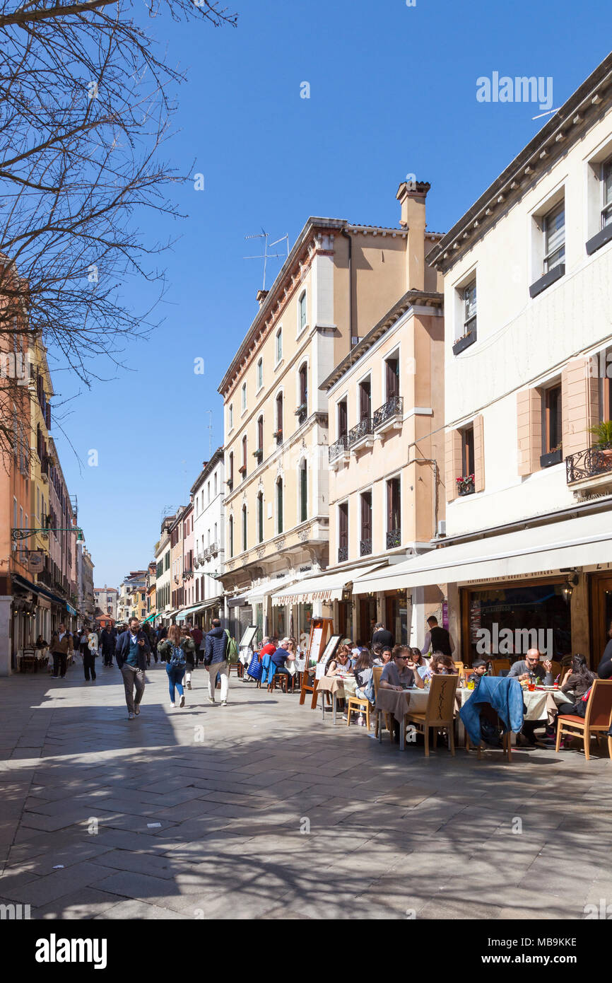 Busy street scene on Strada Nova, Cannaregio, Venice, Veneto, Italy with people eating at restaurants and shopping in the shops and stores in spring Stock Photo