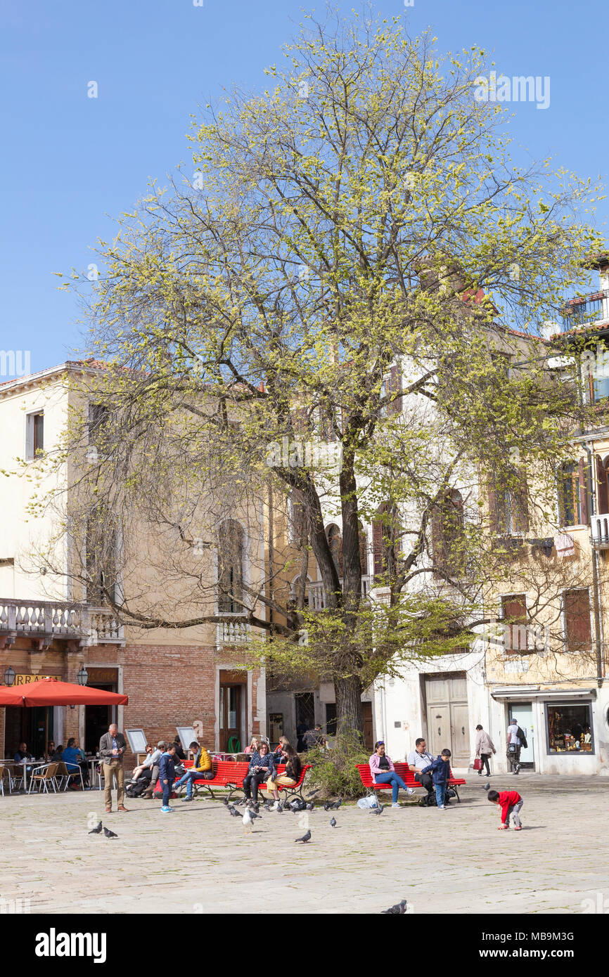 Campo San Polo, San Polo, Venice, Veneto, Italy in spring with Venetian families and their children enjoying the spring sunshine on colorful red bench - Stock Image