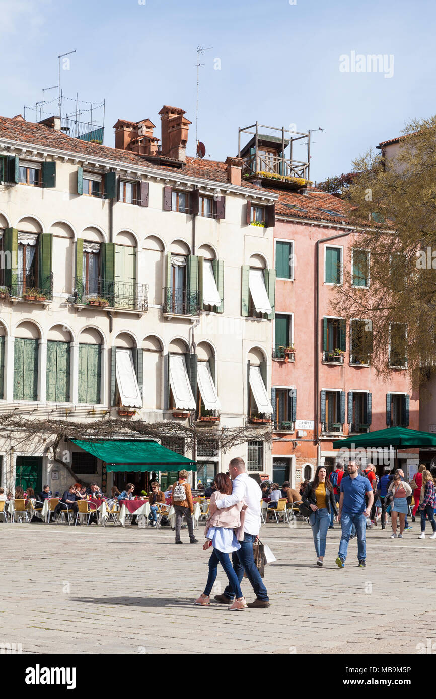Campo San Polo, San Polo, Venice, Veneto, Italy in spring with a loving couple walking arm in arm and people dining at the Pizzeria Bar Cico in the su - Stock Image