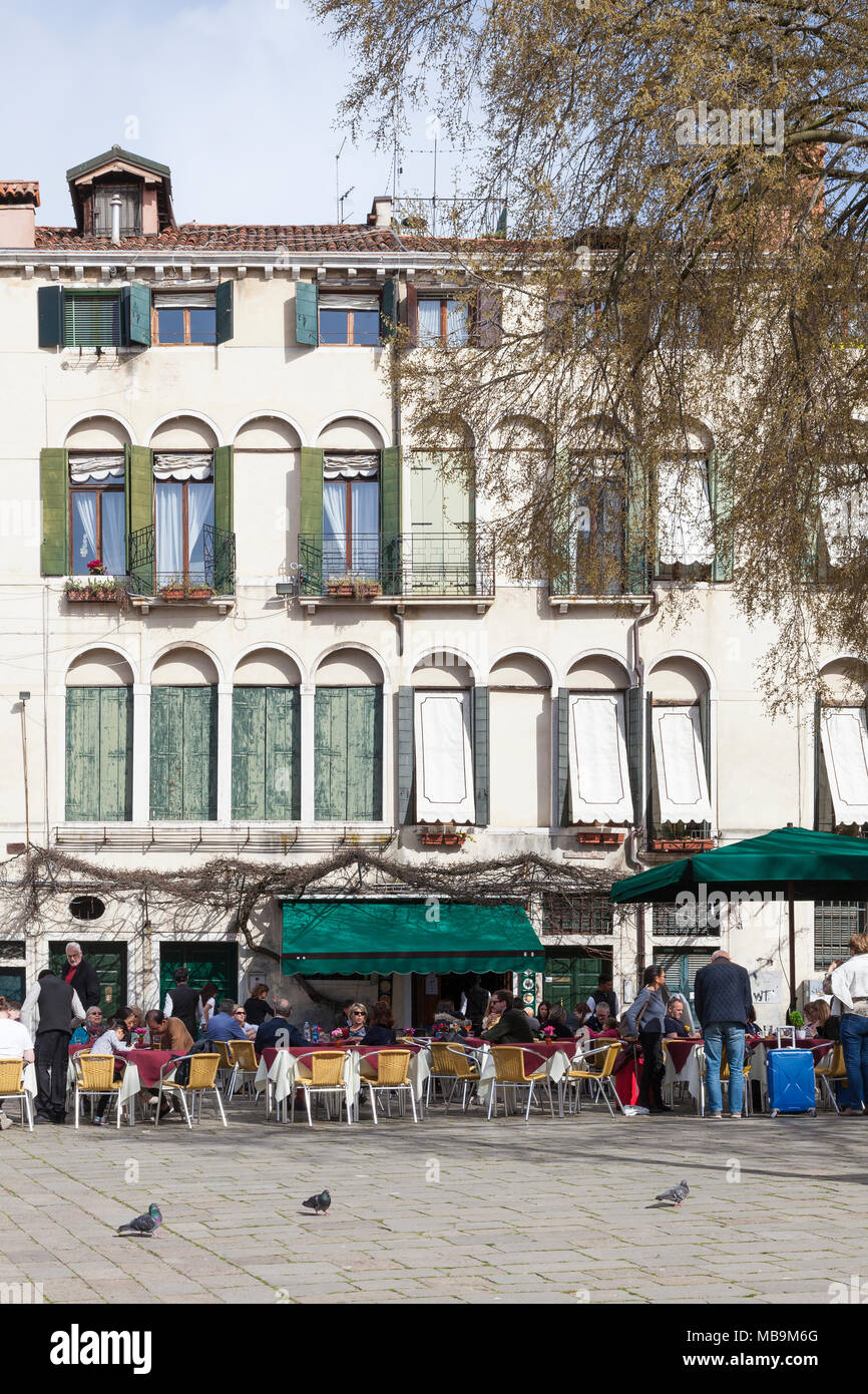 Campo San Polo, San Polo, Venice, Veneto, Italy in spring with locals and tourists eating outdoors at tables at the Pizzeria Bar Cico - Stock Image