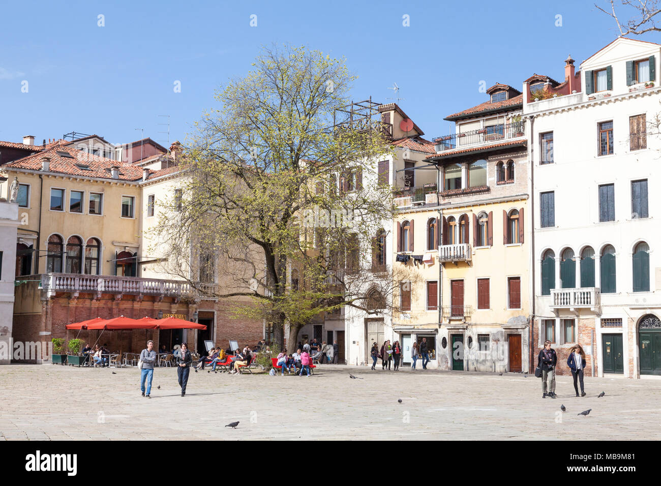Campo San Polo, San Polo, Venice, Veneto, Italy in spring with local Venetians going about daily life  relaxing in the sunshine - Stock Image