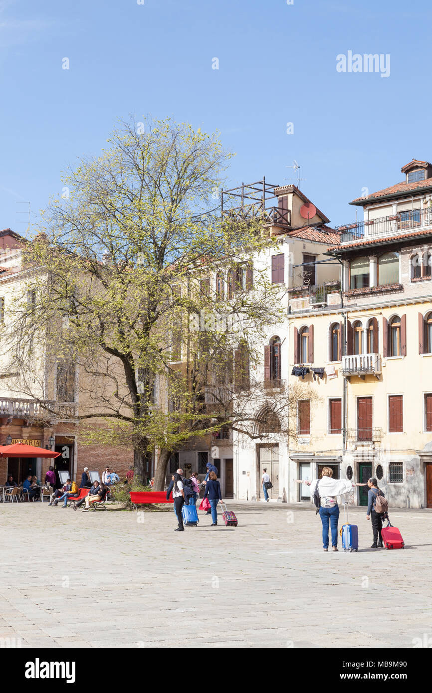 Campo San Polo, San Polo, Venice, Veneto, Italy in spring with tourists pulling their suitcases across the square and locals relaxing under trees - Stock Image