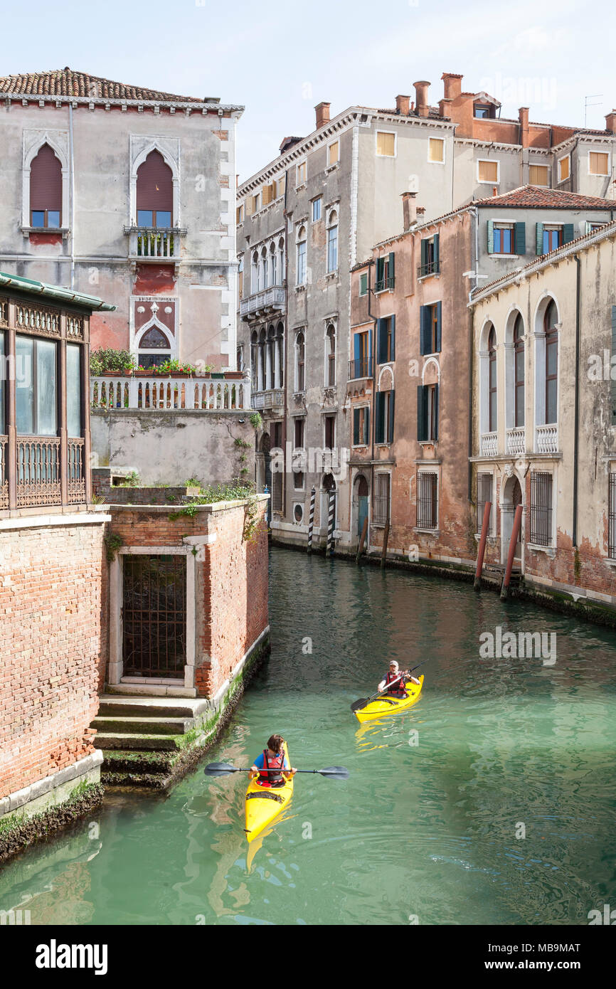 Rio San Polo, San Polo, Venice, Veneto Italy with two yellow rental kayaks  with tourists sightseeing. Vacation activity. Holiday activity. - Stock Image
