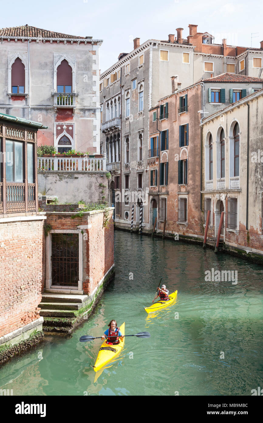 Rio San Polo, San Polo, Venice, Veneto Italy. Two tourists enjoying kayaking and sightseeing back canals in rented kayaks - Stock Image