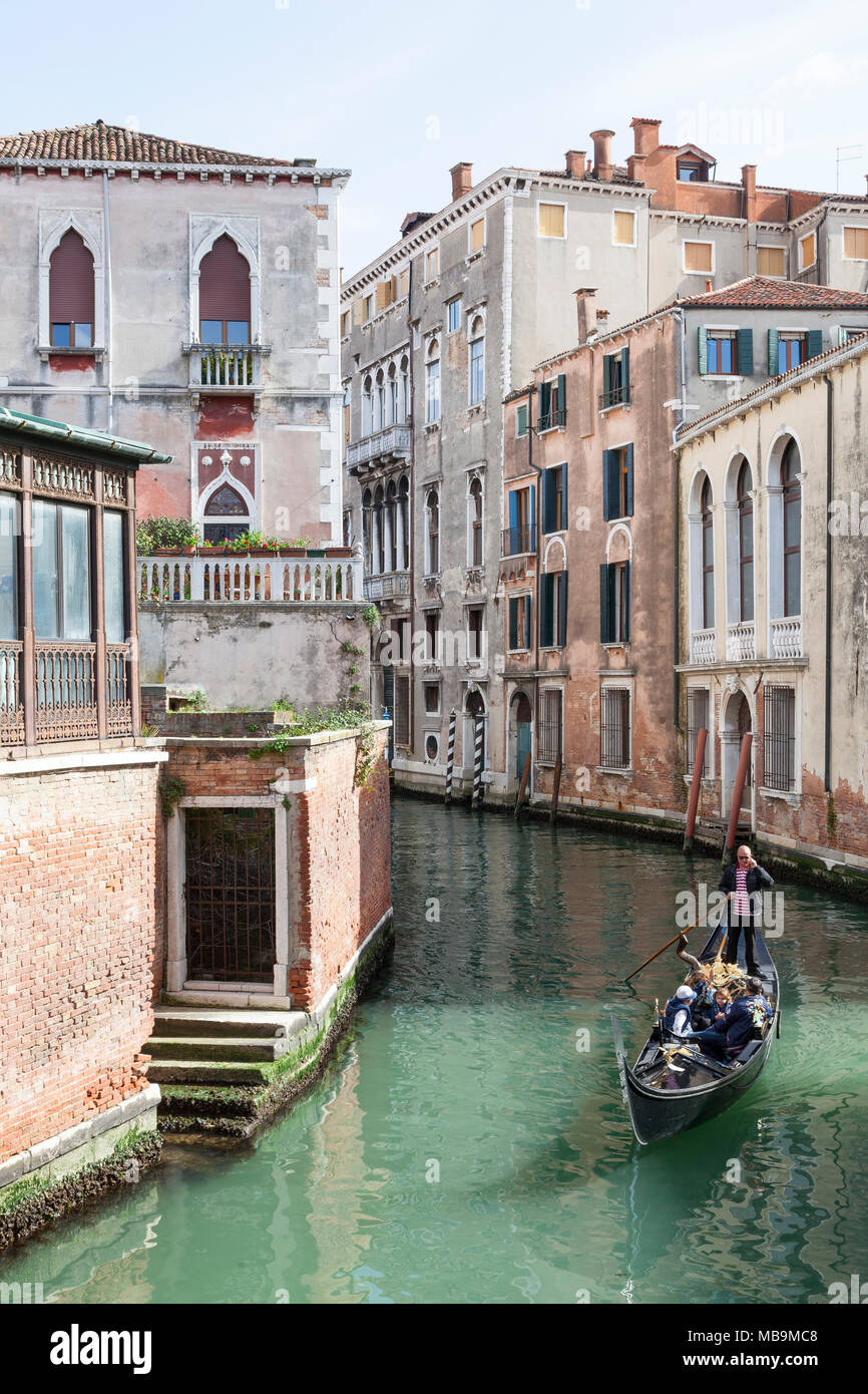 Rio San Polo, San Polo, Venice, Veneto Italy. Gondolier rowing tourists through a picturesque canal in his gondola  on a sightseeing tour - Stock Image