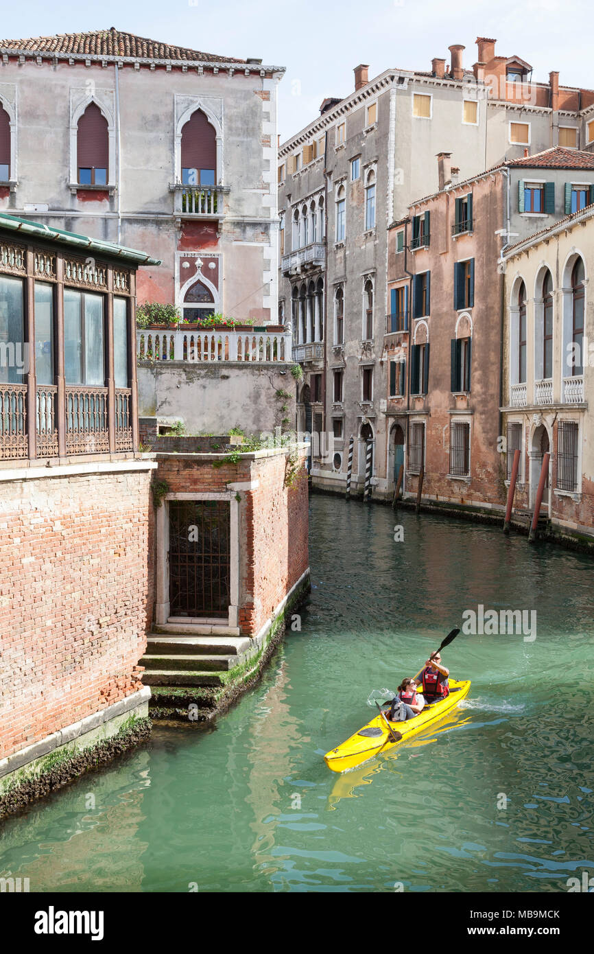 Couple of tourists kayaking on Rio San Polo, San Polo, Venice, Veneto Italy in a rental kayak as they enjoy sightseeing the back canals of the city - Stock Image