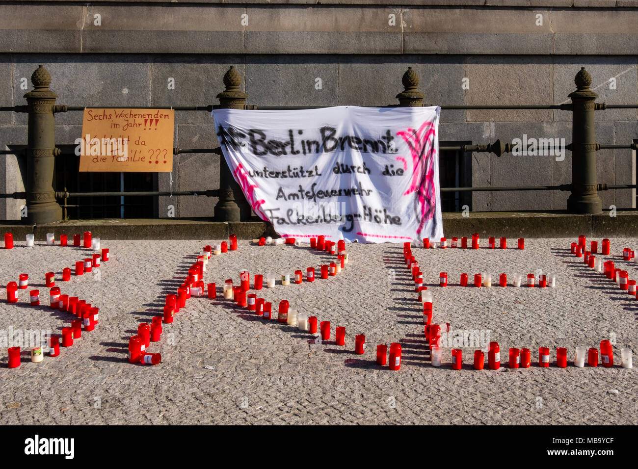 Germany Berlin, Mitte, 8th April 2018. Berlin Firefighters oppose austerity policies of state government in 'Berlin Burns' demonstration in Front of the Red Town Hall Firefighters are protesting about poor working conditions, lack of staff, old equipment and a recently introduced 12-hour shift system. A brazier carries their motto 'Berlin burns' in a symbolic attempt to alert the public to the dangerous situation. The firefighters' protest is directed against the Social Democratic-Left Party-Green Party coalition that runs the Berlin state government. credit: Eden Breitz/Alamy Live News - Stock Image