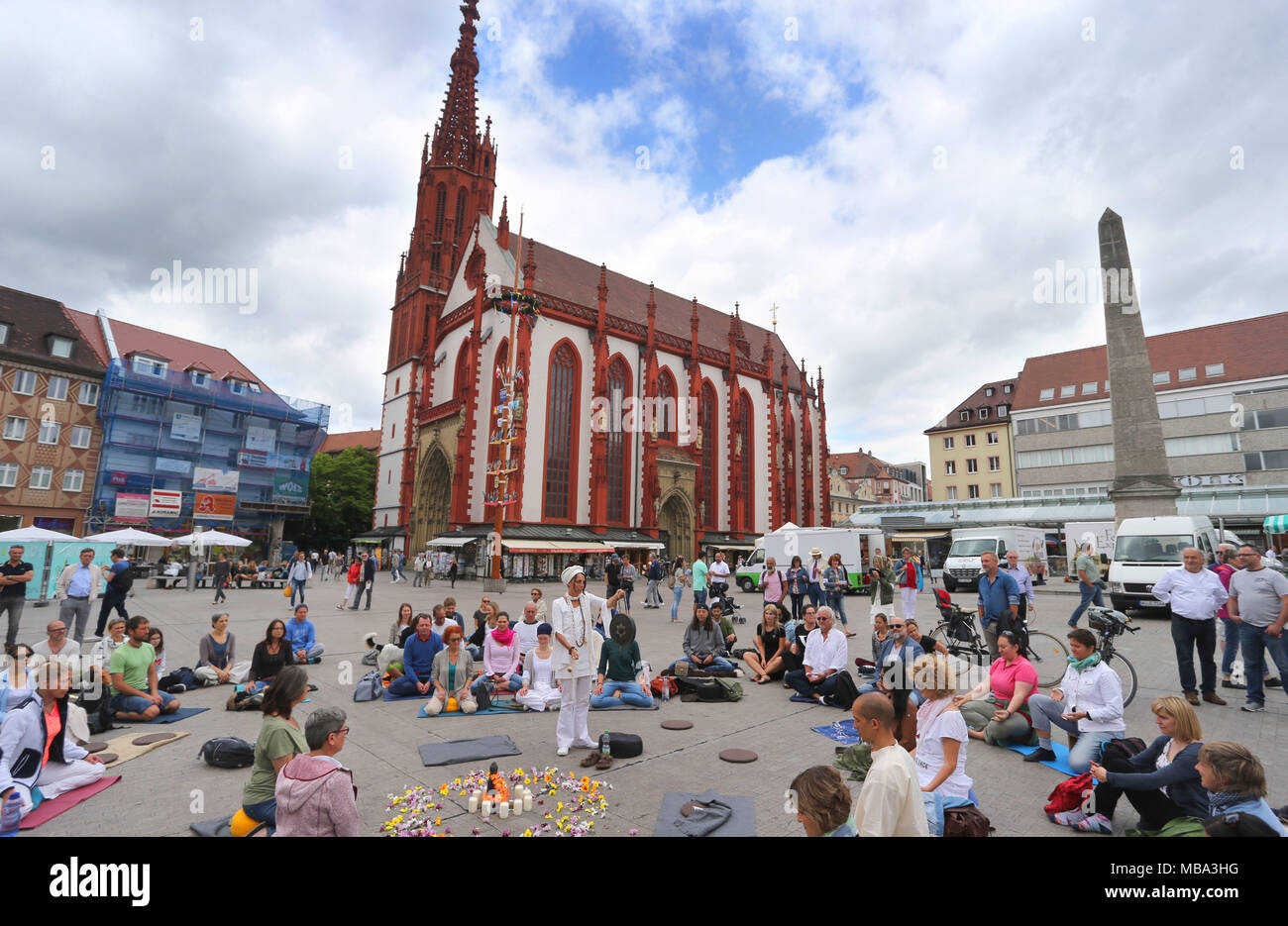 People beginning a meditation flashmob to the sound of a gong, at the Marktplatz in Würzburg, Germany, 17.06.2017. The event's motto was 'meditation for world peace' and its organizers say it is the second of its kind in Germany.   usage worldwide - Stock Image