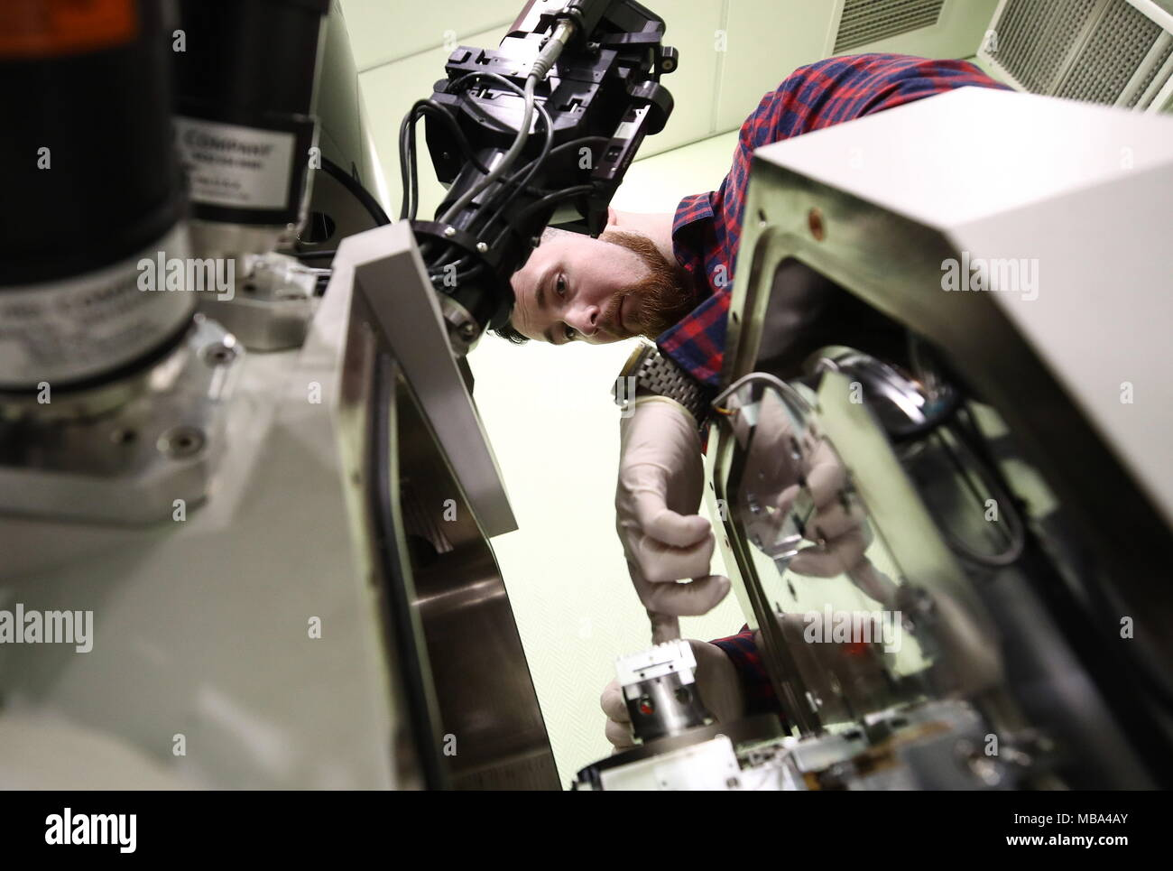 Moscow, Russia. 06th Apr, 2018. MOSCOW, RUSSIA - APRIL 6, 2018: An employee puts a study sample into a scanning electron microscope (SEM) at an electron microscopy laboratory of the Kurchatov Institute National Research Center. Valery Sharifulin/TASS Credit: ITAR-TASS News Agency/Alamy Live News - Stock Image