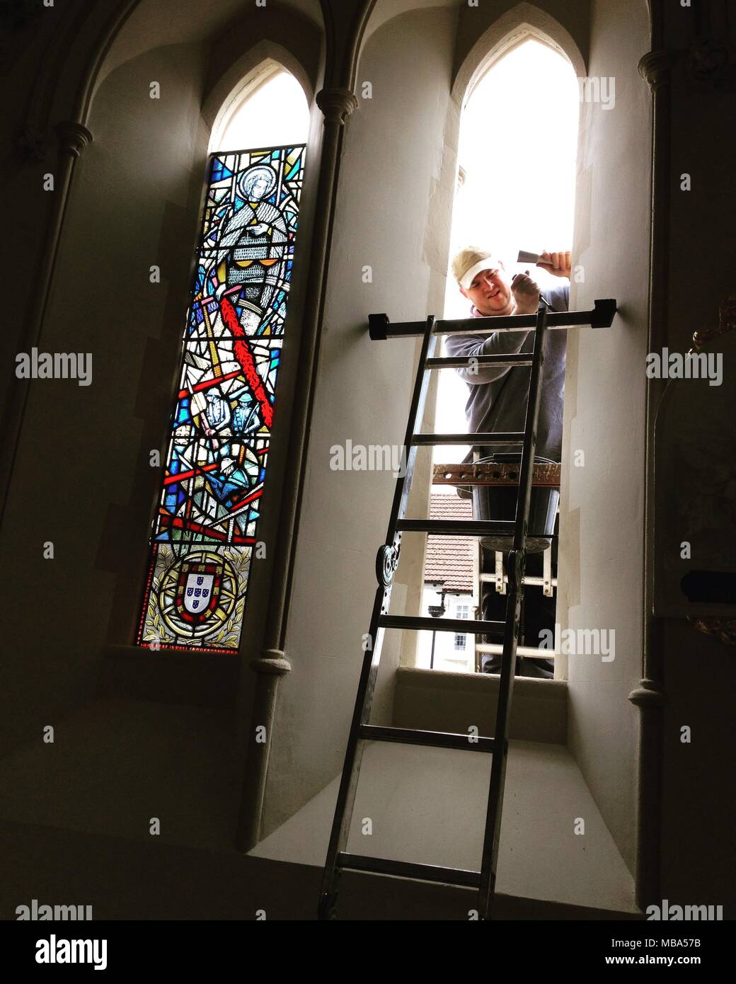 Windows are installed prior to Mass on April 9, 2018, Twickenham UK, to commemorate the centenary of the first very heavy losses of Portuguese soldiers in the First World War, during the Battle of the Lys in Flanders, on April 9, 1918. St. James's Catholic church in Twickenham has commissioned windows by Stained Glass Designers Caroline & Tony Benyon. The windows were then by Bishop John Wilson titular Bishop of Lindisfarne, during during a special Mass. A plaque was unveiled jointly by His Excellency the Ambassador Manuel Lobo Antunes, Portuguese Ambassador to the UK, & by Field Marshal The L - Stock Image