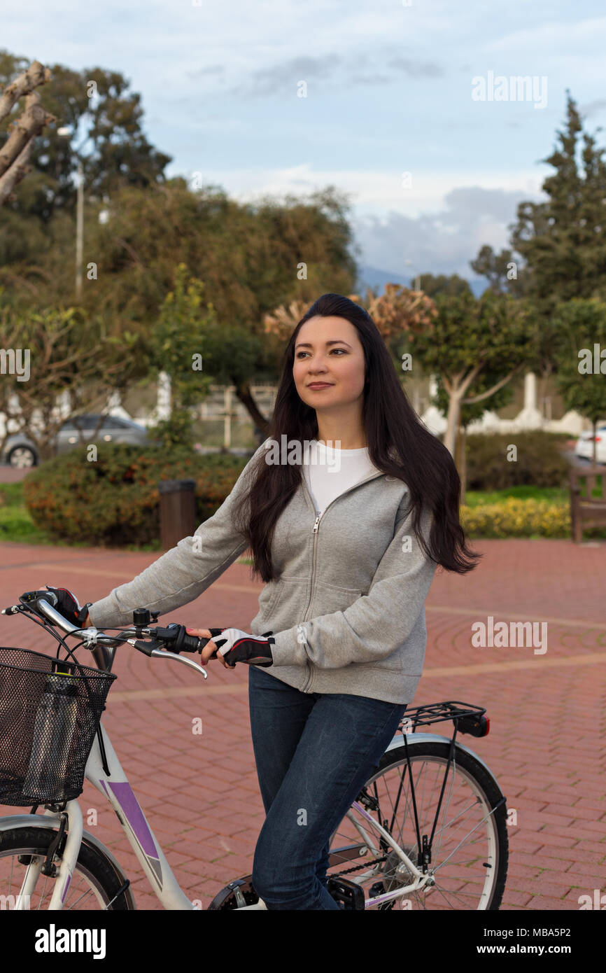 8dc44819671a Healthy lifestyle concept. Self-confident female near bicycle with ...