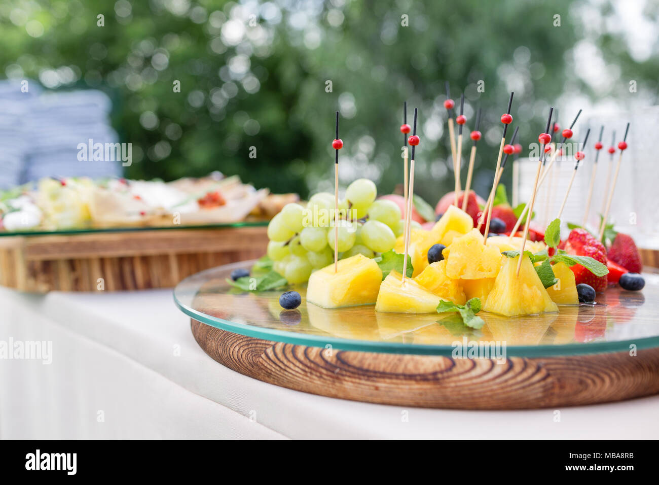 Wooden plate with sliced fruits and berries on a buffet table. Summer party outdoor. Horizontal photo - Stock Image