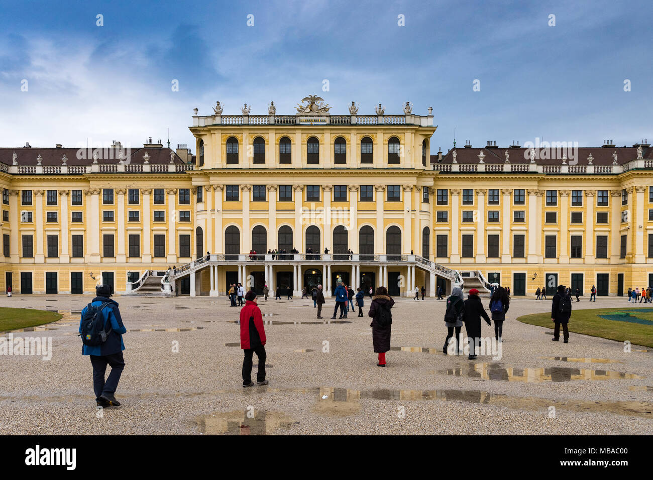 The garden park in Shonbrunn Palace (Wien) in rainy day with small puddles and large groups of tourists walking around - Stock Image