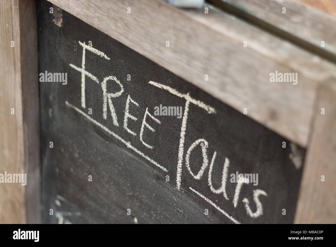 An a-board a-frame sign that says free tours in chalk - Stock Image