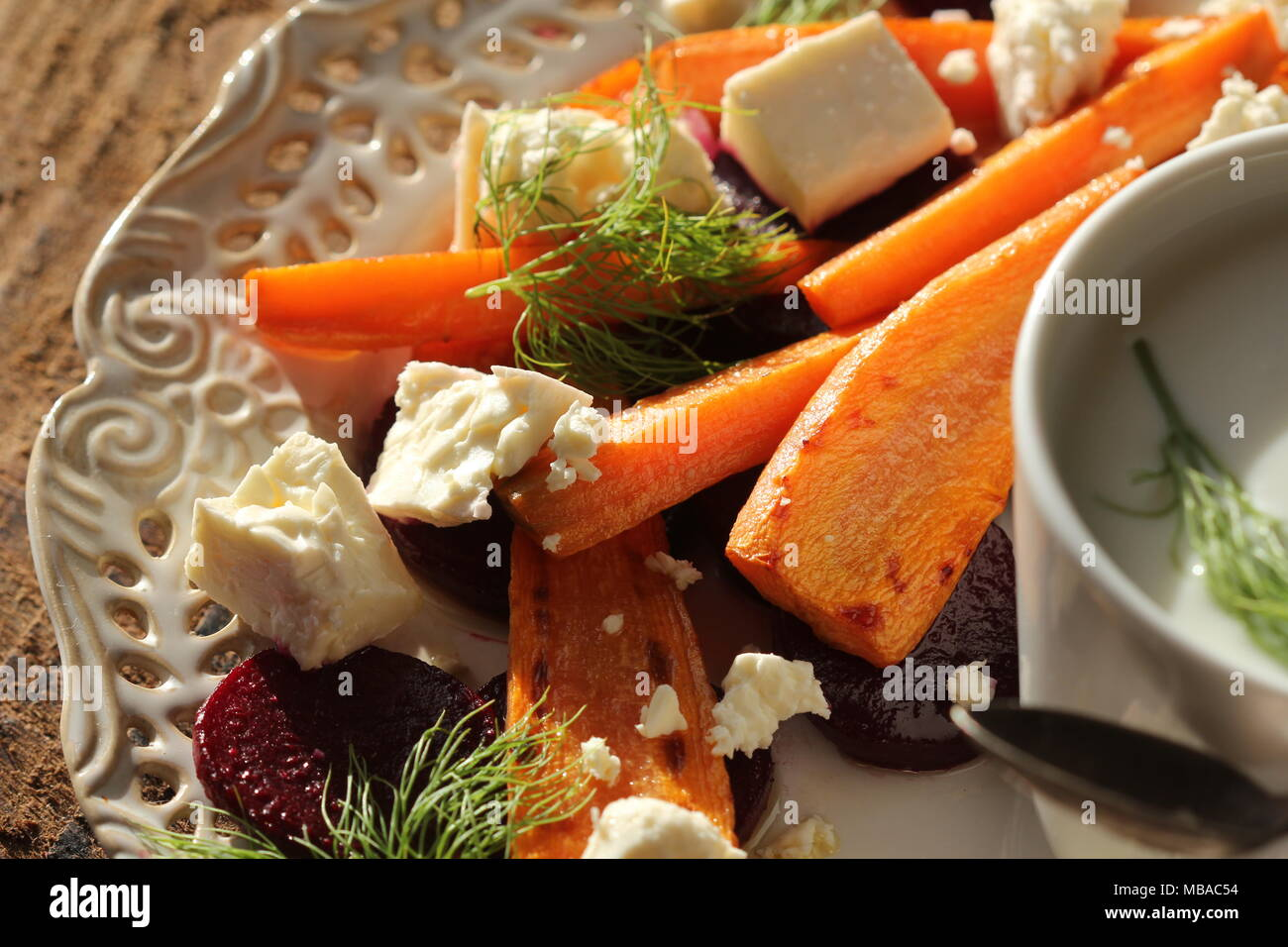 Healthy grilled beet, carrots salad with cheese feta, fennel and Greek yogurt in small glass bowls on the rustic wooden table, top view - Stock Image