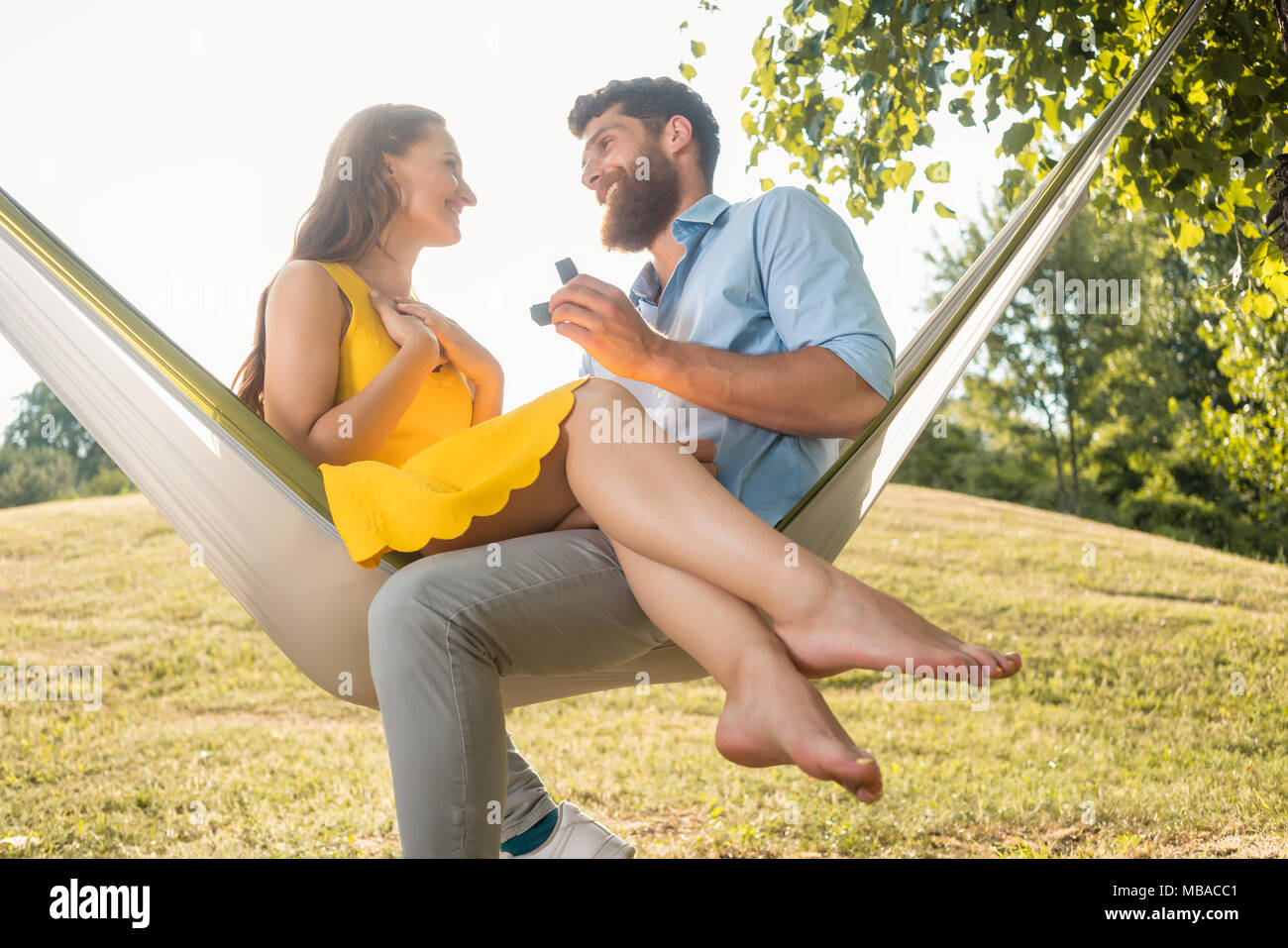 Young man making marriage proposal to beautiful girlfriend - Stock Image