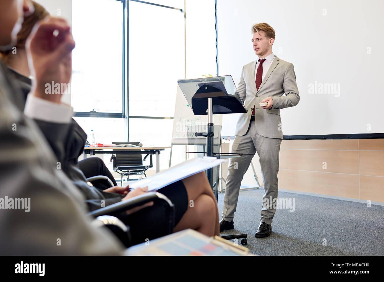 Confident Businessman at Podium - Stock Image