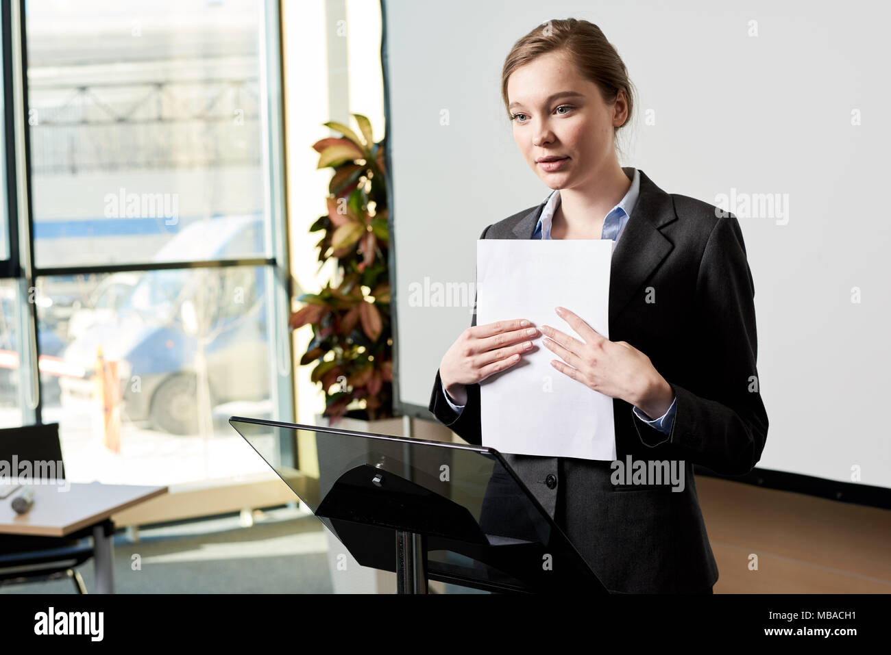 Young Businesswoman Giving Speech at Forum - Stock Image