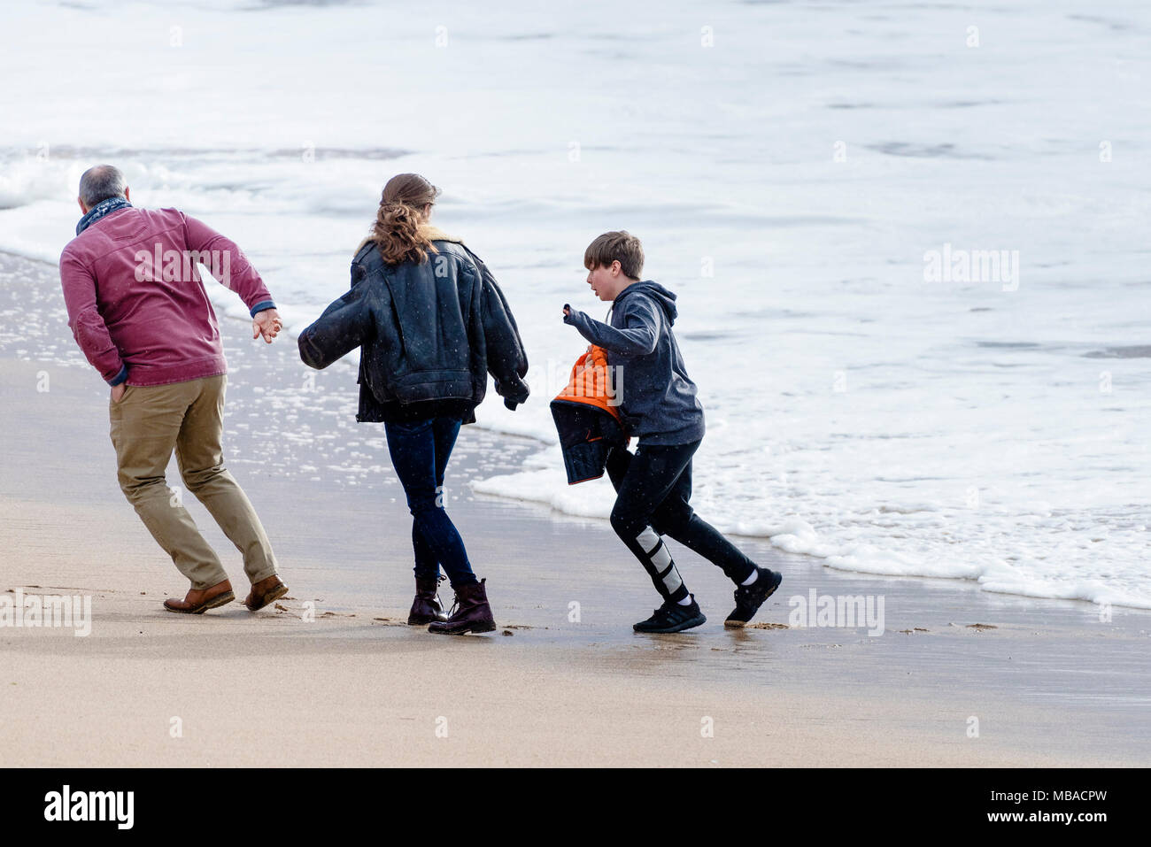 Holidaymakers nearly caught by the incoming tide at Fistral beach in Newquay Cornwall. - Stock Image