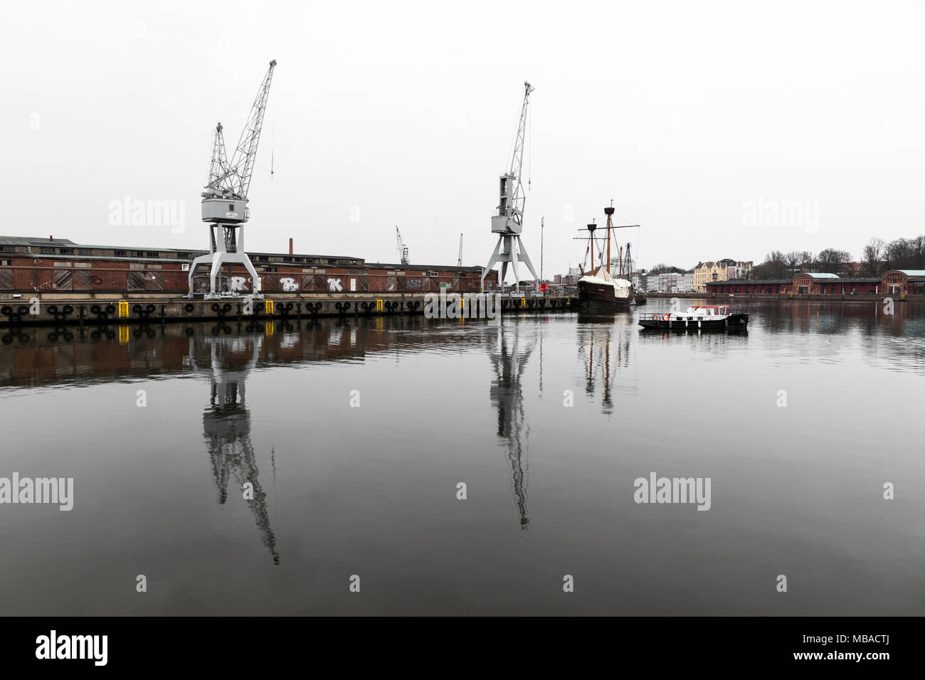 Lubeck, Germany. Boat and cranes at the harbor in the river Trave in Lubeck - Stock Image