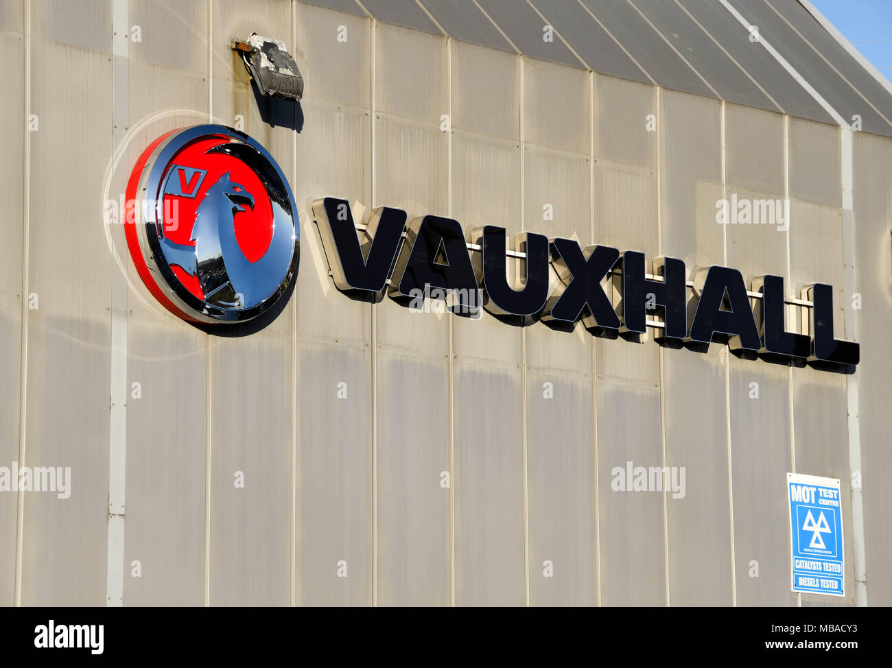 Corporate logo of Vauxhall on the side wall of a car showroom - Stock Image