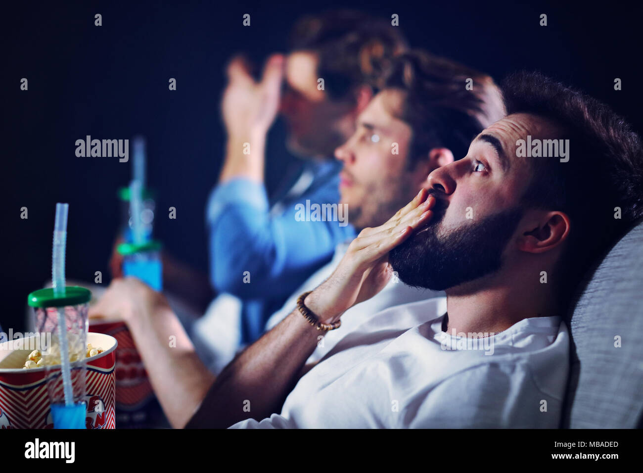 Group of happy friends sitting in cinema watch film and eating popcorn Stock Photo