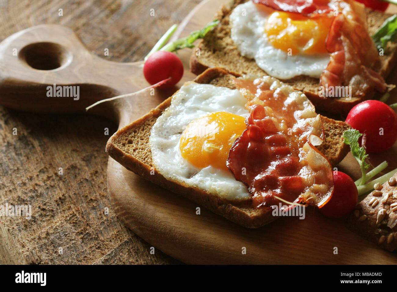 Breakfast of crispy bacon, fried eggs and bread. Sandwiches on cutting board. Rustic table Stock Photo