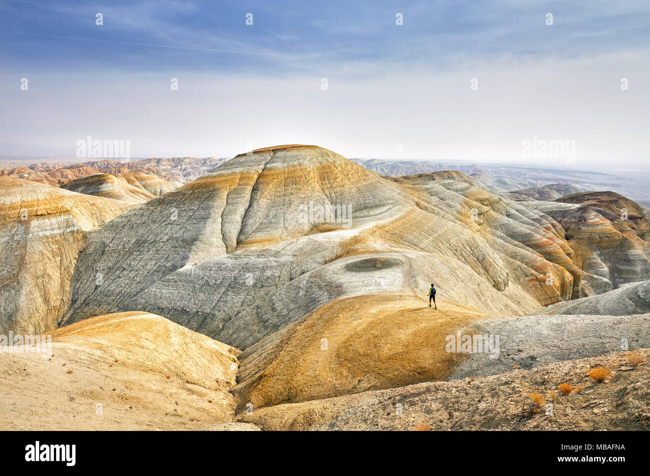 Tourist walking at the trail on surreal yellow mountains in desert park Altyn Emel in Kazakhstan - Stock Image