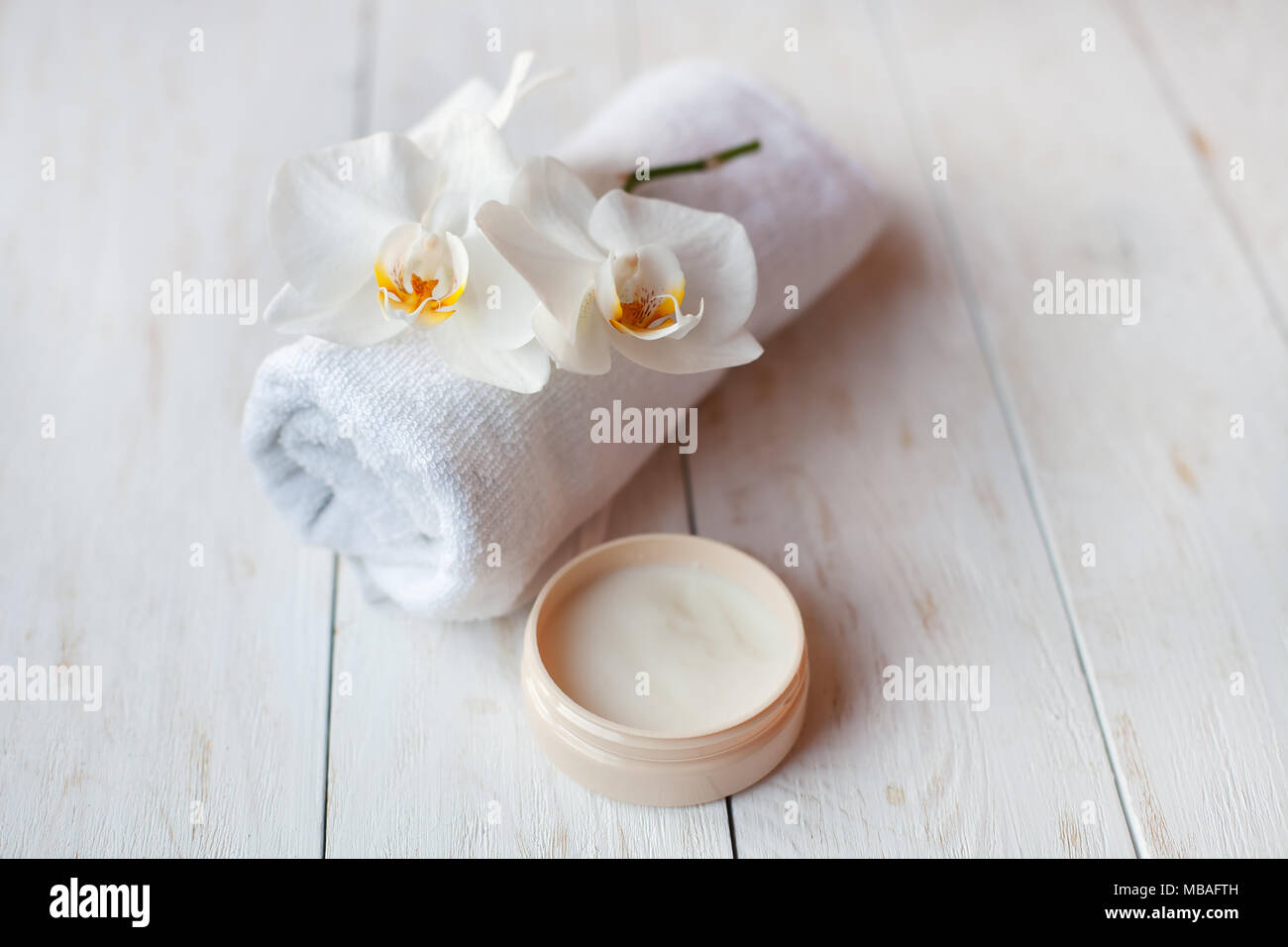 face cream with white orchid and  towel  on white wooden table. - Stock Image