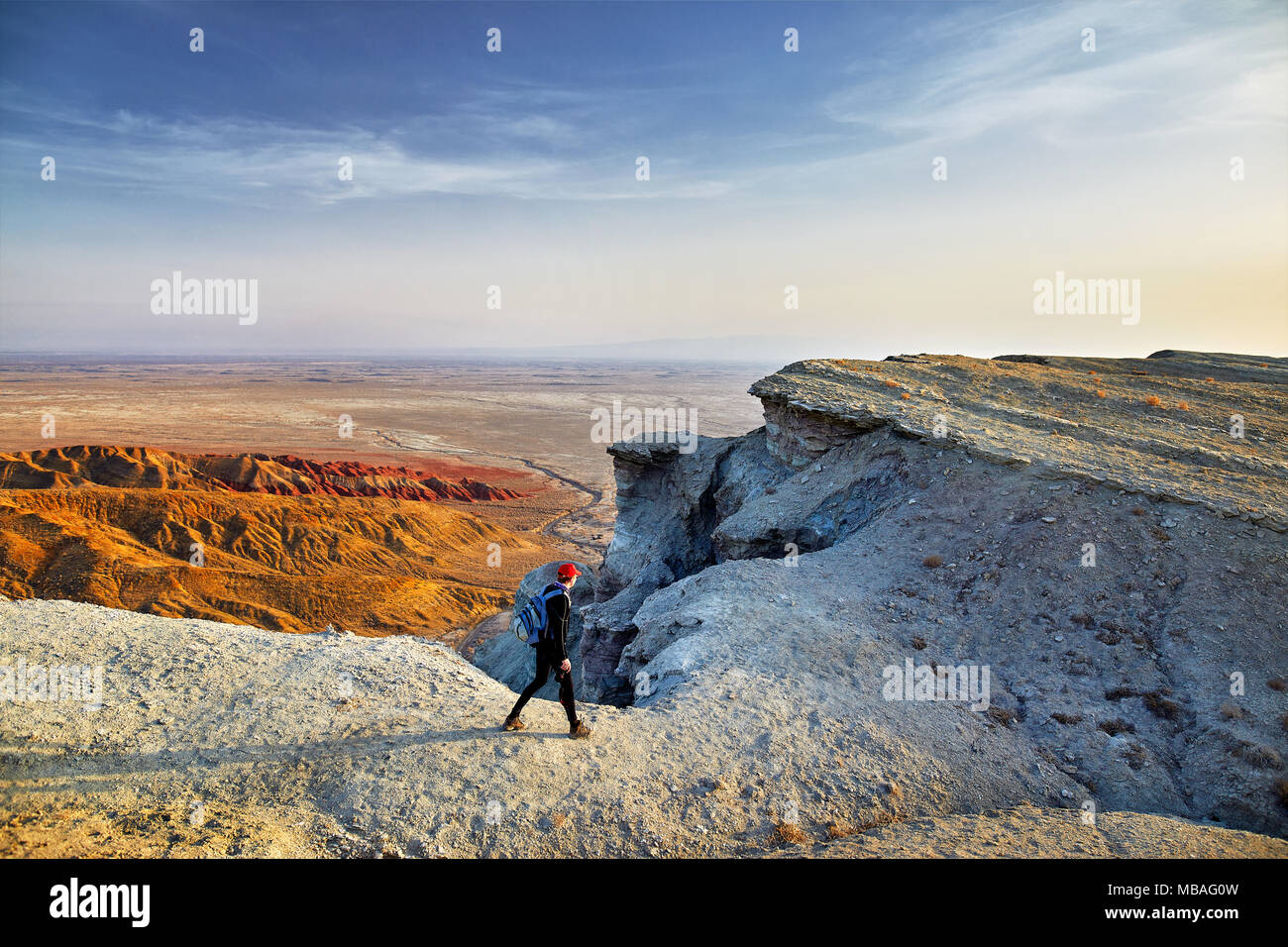 Tourist walking at the on surreal white mountains in desert park Altyn Emel in Kazakhstan - Stock Image