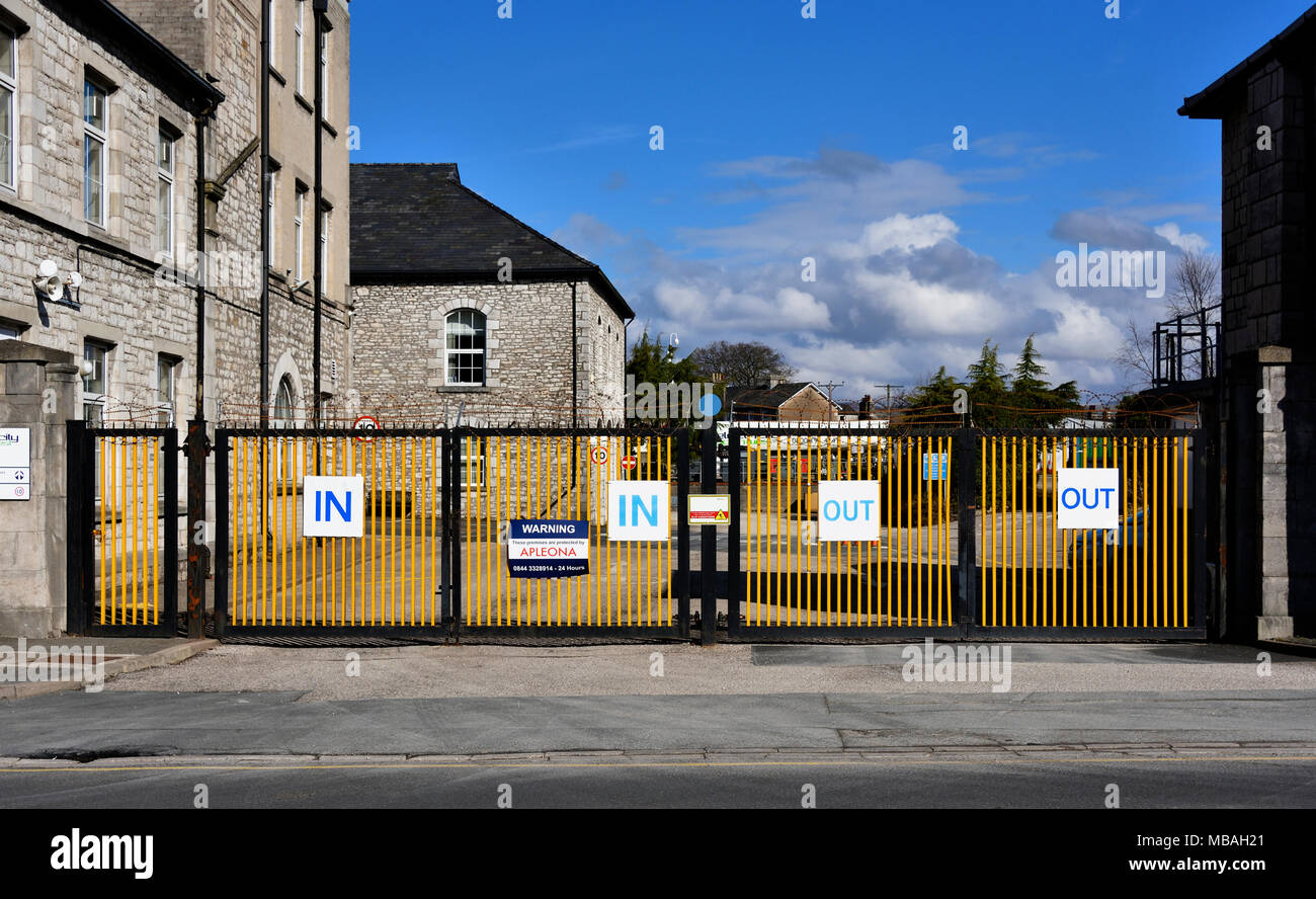 'IN' and 'OUT' signs on metal gates to industrial site. Parkside Road, Kendal, Cumbria, England, United Kingdom, Europe. - Stock Image