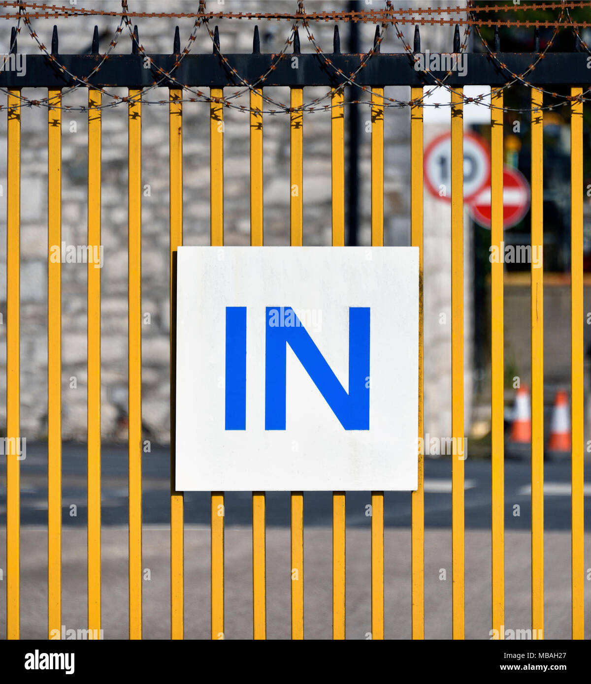 'IN' sign and razor wire on metal gate to industrial site. Parkside Road, Kendal, Cumbria, England, United Kingdom, Europe. - Stock Image